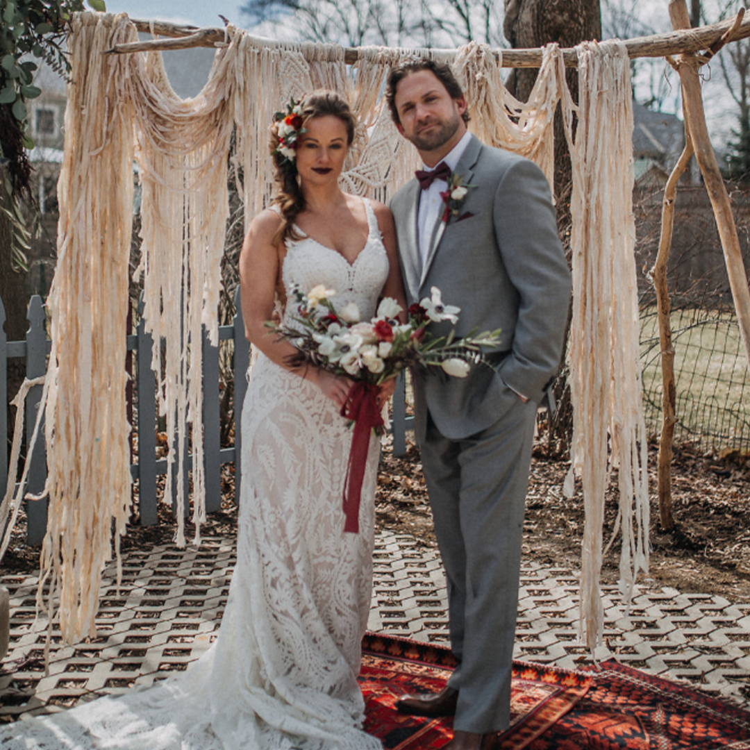 Bride and groom posing for a picture with a rustic feel