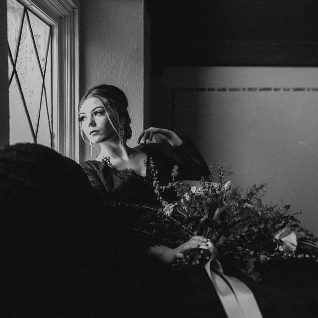 Bride looking out a window with large flowers