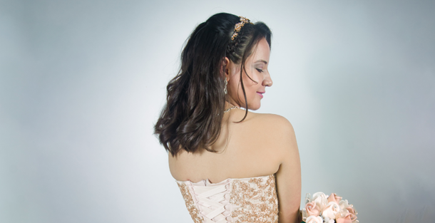 Bride in a studio with a half updo, headband and flowers